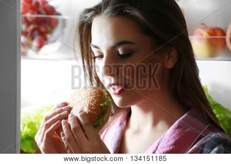 Young beautiful woman eating unhealthy food from the fridge at night