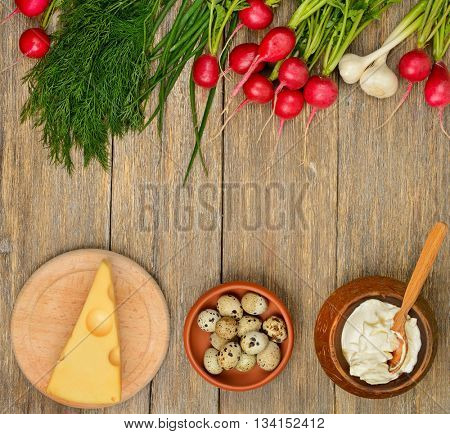 Healthy food (vegetables, cheese, egg, sour cream) on old wooden table. Top view.