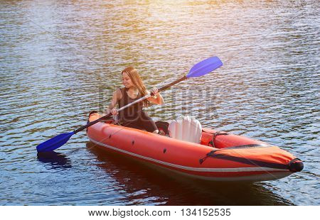 The smiling girl -the sportswoman with longdark hair in blacksportswear rows with an oar on the lake in a red inflatable canoe in a warm summer sunny day. Occupation by sports rowing on a kayaking.