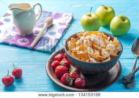 Cornflakes in a bowl with milk apple and strawberry on the wooden table