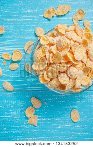 cornflakes on blue wooden table at morning top view