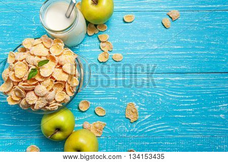 Bowl of cornflakes cereal on a blue wooden table and fresh apple milk behind. Horizontal image with copy space.
