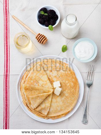 Thin crepes or pancakes with butter, honey and sour cream on a rustic textile background Top view.