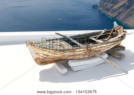 Old wooden boat on the white terrace in the village Oia. Greece. Santorini.