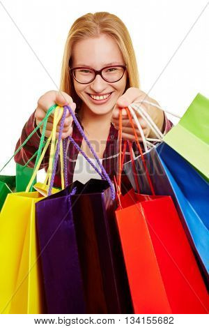 Happy woman carries a lot of colorful shopping bags with her hands