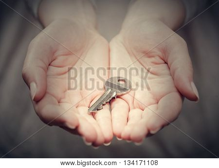 Key in woman's hand in gesture of giving. Strong spotlight. Concept of success in live, business solution, real estate industry etc.