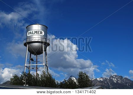 Palmer, Alaska water tower in May against a beautiful blue sky and snow topped mountains