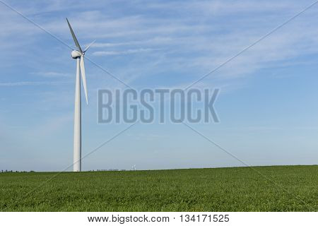 A wind generator in a grassy field.