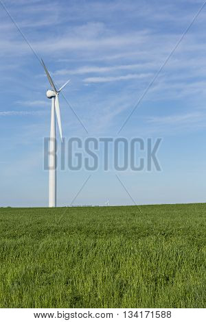 A wind generator in a grassy field.
