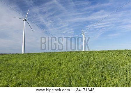 A pair of wind generators in a field.