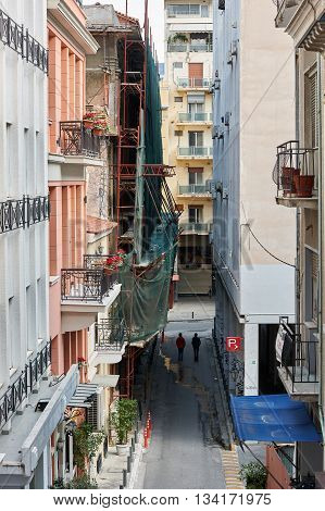 ATHENS, GREECE - circa APR 2016: Elevated view of typical street in central Athens Greece with two friends walking towards intersection