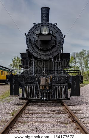 An old railroad steam locomotive on track.
