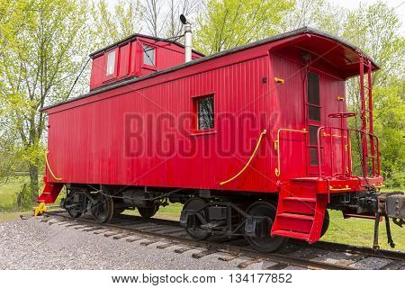 An old red wooden railroad caboose on track.