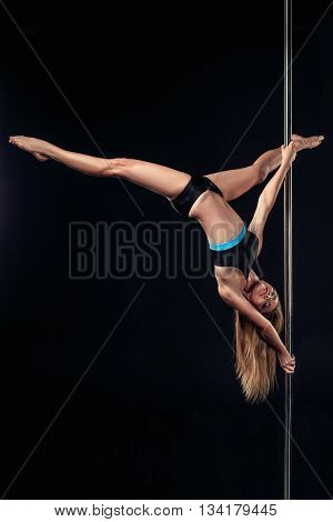 Pole dancer. Young pretty woman on pole on black background
