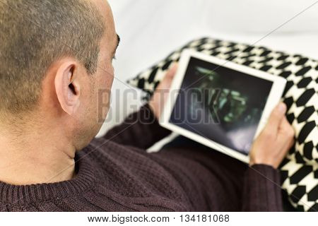 a young caucasian man lying on the couch watches a movie or a series in streaming in his tablet computer