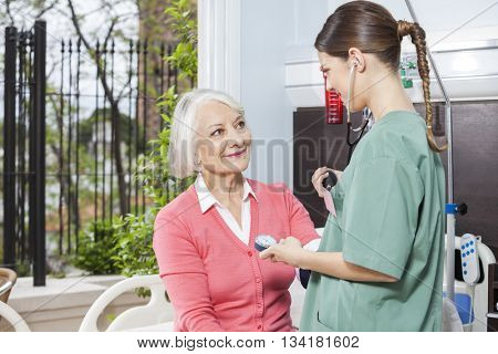 Nurse Examining Blood Pressure Of Senior Patient