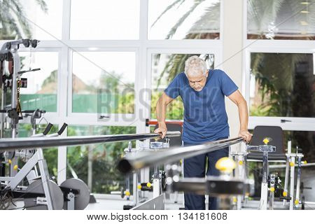 Senior Man Taking Support Of Bars At Rehab Center