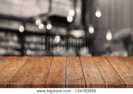 Wooden tabletop with sepia coffee shop blurred background, stock photo
