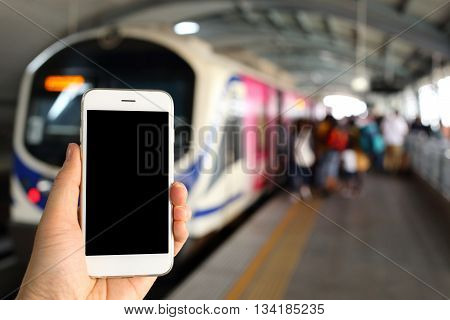 Hand holding smartphone with subway station background