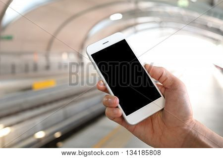 Hand holding smartphone with railway station background