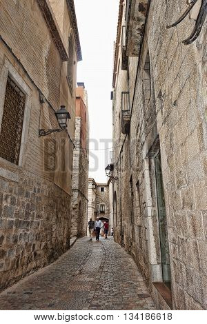 GIRONA SPAIN - JULY 17 2013: The narrow streets of the ancient quarter in Girona on July 17 2013. Well preserved since the Middle Ages the historic core of the city attracts a significant number of tourists