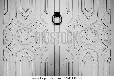 a white carving wood door with black ring handle