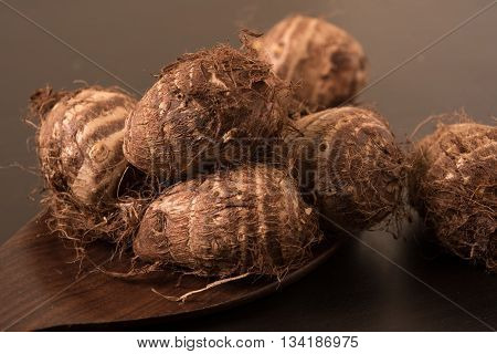Heap of fresh taro roots (colocasia) on wooden spoon