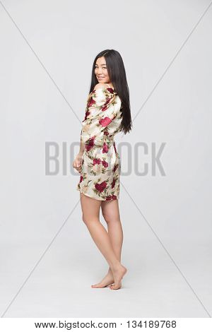 Potrait of fashion asian lady in spring or summer dress osng in full length in studio. Happy brunette looking at camera.