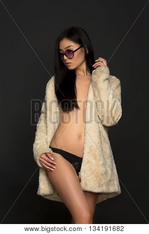 Portrait of fashion asian model in sunglasses over grey bakground. Beautiful woman in black lingerie and white coat in studio.