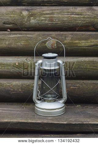 kerosene oil lamp near wood wall close up
