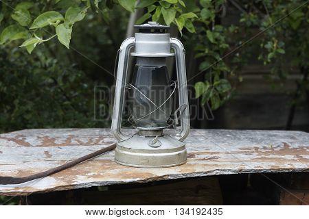 kerosene oil lamp on roofing slate and apple tree close up