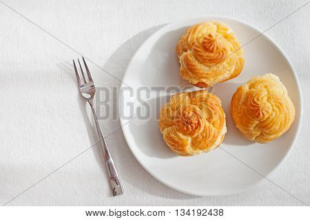 Profiteroles, choux with a custard cream, creme anglaise, whipped cream, dessert on a white plate Copy space Top view