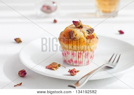 Muffin, mini cake, cup cake on a white plate with a rose buds tea on a white textile background