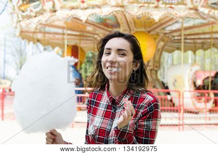 Summer lifestyle fashion portrait of young stylish hipster woman walking on street, and eating cotton candy