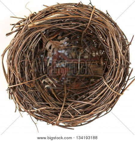 A brown empty bird's nest made of twigs.