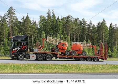 PAIMIO, FINLAND - JUNE 3, 2016: Black Scania truck transports two aerial work platforms on lowboy trailer along freeway in South of Finland.