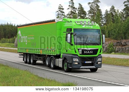 PAIMIO, FINLAND - JUNE 10, 2016: Lime green MAN TGX 28.520 cargo truck moves along motorway in South of Finland at summer.