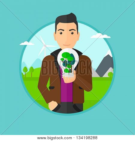 Man holding light bulb with tree inside. Man with light bulb and tree inside standing on a background with wind turbines. Vector flat design illustration in the circle isolated on background.