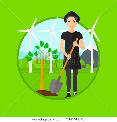A woman plants a tree. Woman standing with shovel near newly planted tree. Woman planting tree on a background of wind turbines. Vector flat design illustration in the circle isolated on background.
