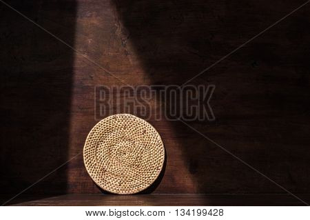 Low key, Round weave rattan tray, countryside household, on retro wooden background with shade and shadow, shadow environment at surrounding