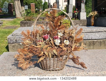 decorative wicker basket with sear flowers and twigs on the cemetery