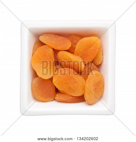 Dried apricots in a square bowl isolated on white background