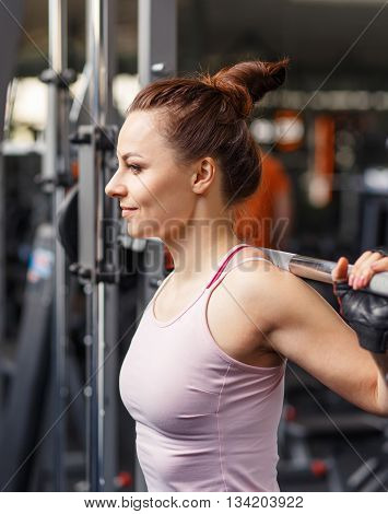 Young Smiling Woman Squatting With Barbell In Gym