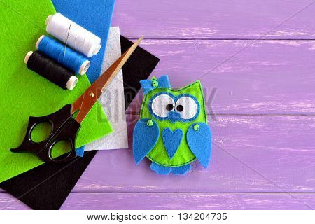 Owl toy is sewn from plush felt. Green fabric owl with blue heart and bow. Home decor idea for beginners and children. Frugal and fun hobby. Colored felt sheets, scissors, thread, needle