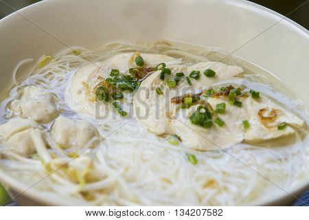Thai noodle soup with fish ball in white ceramic bowl on brown wooden table - close up top view