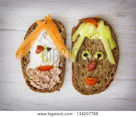 Two funny faces made of bread butter tuna sausage carrot paprika tomato and black pepper. Humorous food. Food show. Smiling faces. Creative food. Facial expression.
