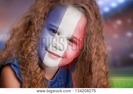 Soccer fan little smiling girl portrait with France flag on face