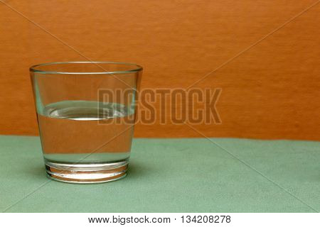 a glass of water on colored background