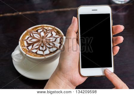Close up of a woman using mobile smart phone in coffee shop.
