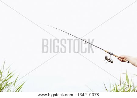 Close-up shot of man hand holding rod and spinning reel on summer lake - fishing concept with copy space
